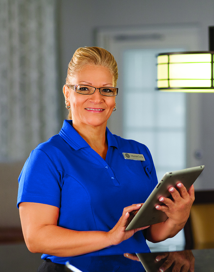 Supervisor. Women in a royal blue polo holding a tablet.   MasterCorp