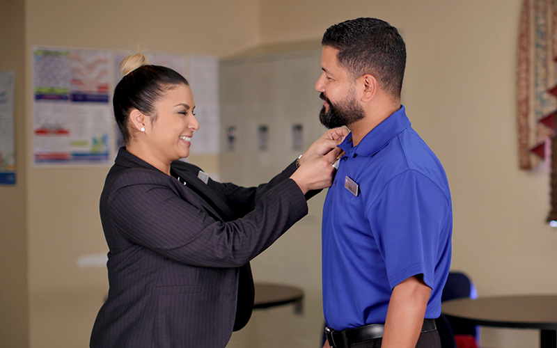 Pinning ceremony between female manager and male employee | MasterCorp