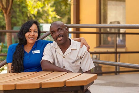 Our People - A Spanish female and African American male co-workers sitting together smiling.   MasterCorp