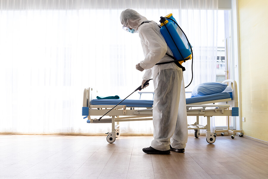 Commercial Services - Hospital room being cleaned by staff in protective suit. | MasterCorp