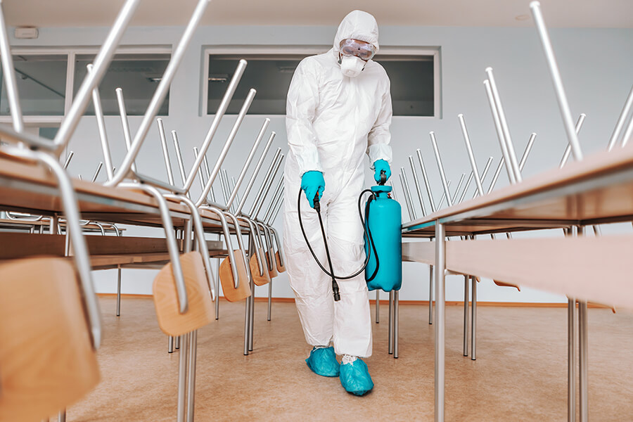 Commercial Services - A room being sanitize by a person in sterile uniform holding sprayer. | MasterCorp