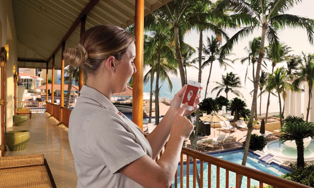 Master Mind Mobile: A housekeeper at a resort holding a cellphone interacting with an app. News | MasterCorp