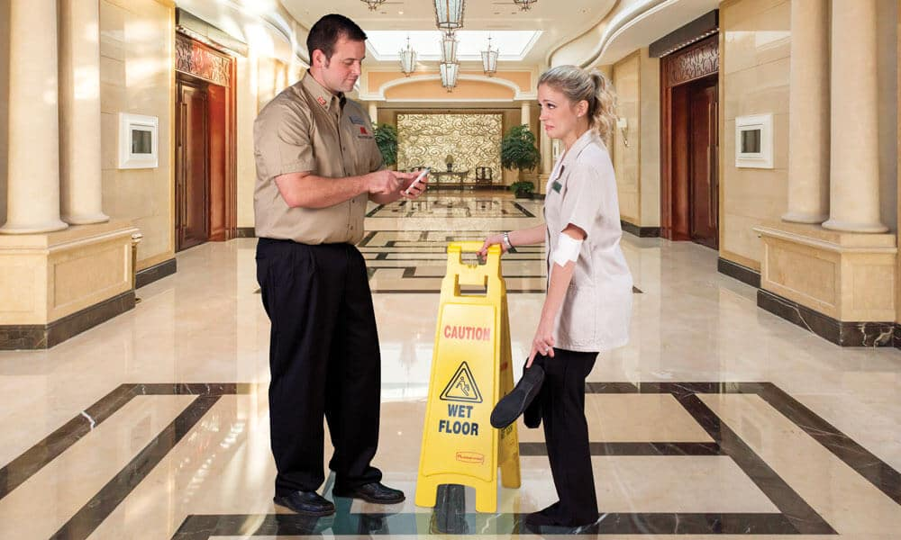 Caution wet floor sign held by a housekeeper standing in front of a supervisor. News | MasterCorp
