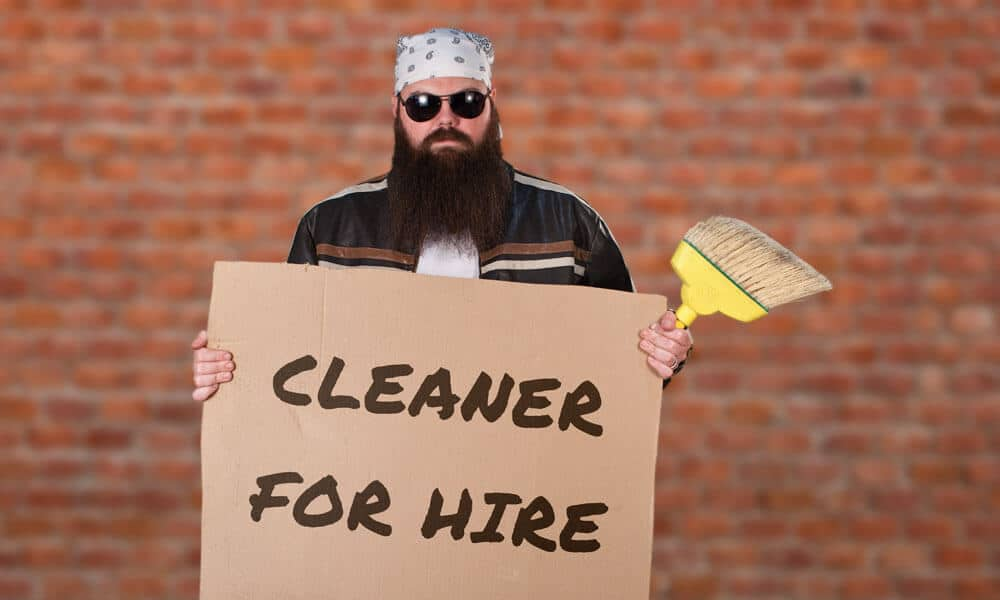 Temp Labor: Biker man holding a sign that says, 'cleaner for hire.' News | MasterCorp